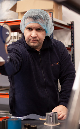 an image of a man, a foxpak employee with a hair net on whilst working on products packaging design