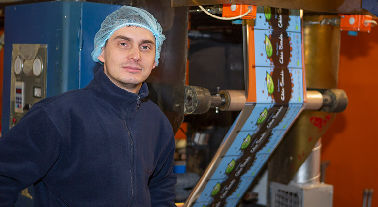 an image of a man, an employee of foxpak wearing a hair net whilst overseeing the printing of packaging