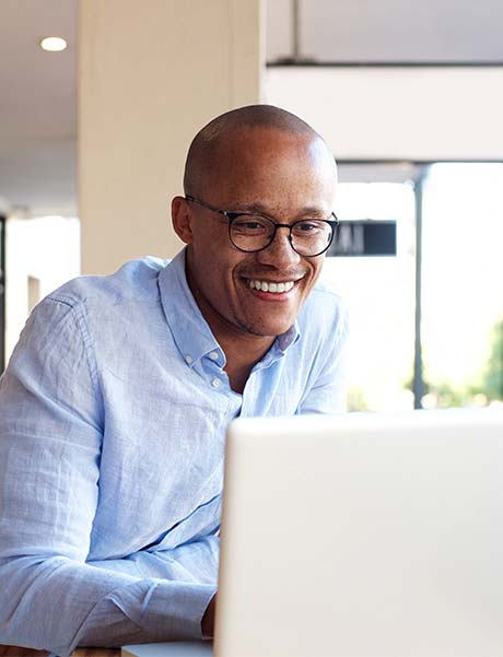An image of a man smiling while he works on his laptop